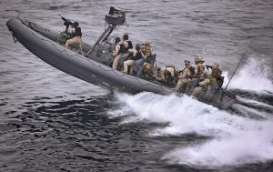 army crew and coast guards on speed boat in action