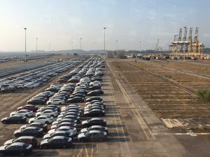 many cars parked at port filling up half the space with cargo containers at the background