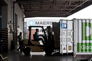 man driving forklift fitting boxes into cargo container