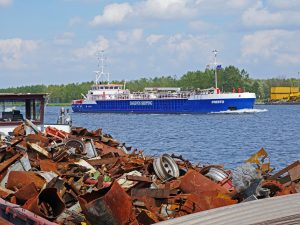 dagevos ship passing through a canal with rusty scrap materials lying on the side of the bank