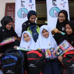 happy group of malay girls receiving PTP backpacks, holding onto wrapped gifts