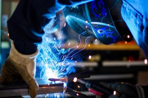 man with glove and mask welding steel, blue lightwaves emission on contact