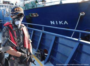 Indonesia marine police guard holding gun on a ship