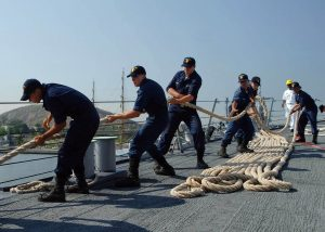 a group of sailors hard at work pulling rope in unison