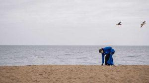 man in blue sweater picking up ocean debris