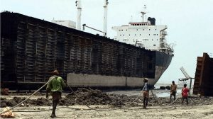 ship breaking with Indian labourers in line with rope over their shoulder