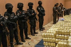 policemen guarding a load of synthetic drugs with a group of officers deliberating the next move