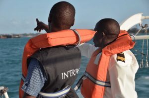 sailors with life jacket pointing towards the ocean