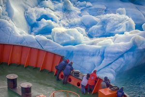 Arctic Ocean climate change, people on ship taking images of sea ice and water