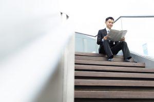 Chinese man reading newspaper sitting on steps singapore china economy coronavirus covid 19