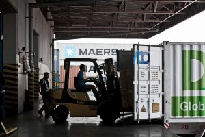 maersk men driving forklift with boxes filling up container