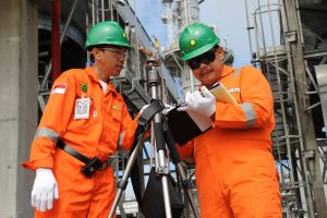 safety officers analysing the checklist board on hand about BP oil gas carbon emission greenhouse gases
