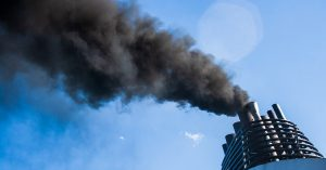 shipping emission of black smoke fumes into clear blue sky
