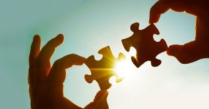 two hands of businessman to connect couple puzzle piece with sky background, symbol of association and connection.business strategy, collaboration and partnership
