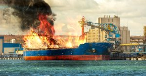 cargo ship at port, burning bright with fire ablaze, smokey black fumes.