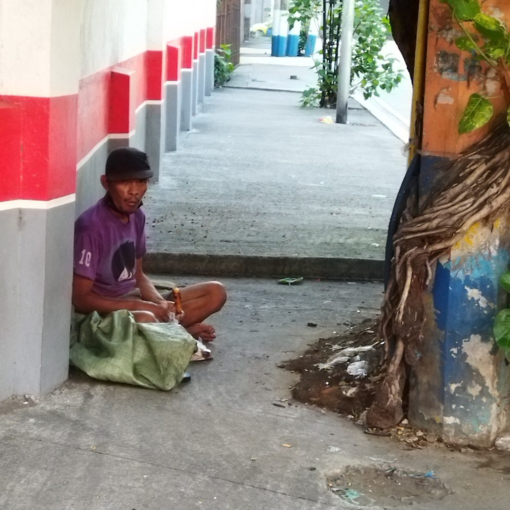 homeless filipino man without identity, sitting on the side of the pavement