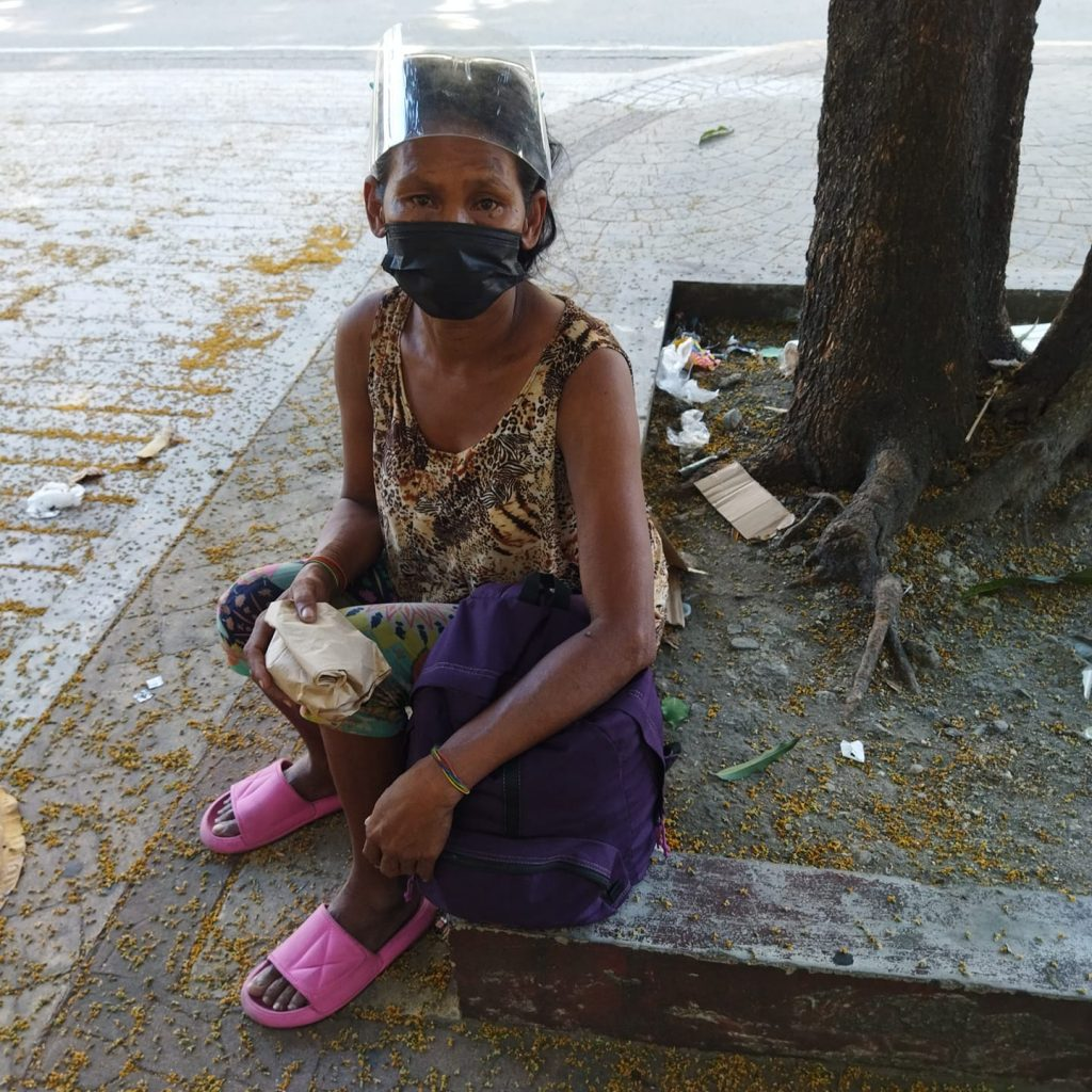 homeless filipino wearing face mask, sitting by the border of a tree, on the street
