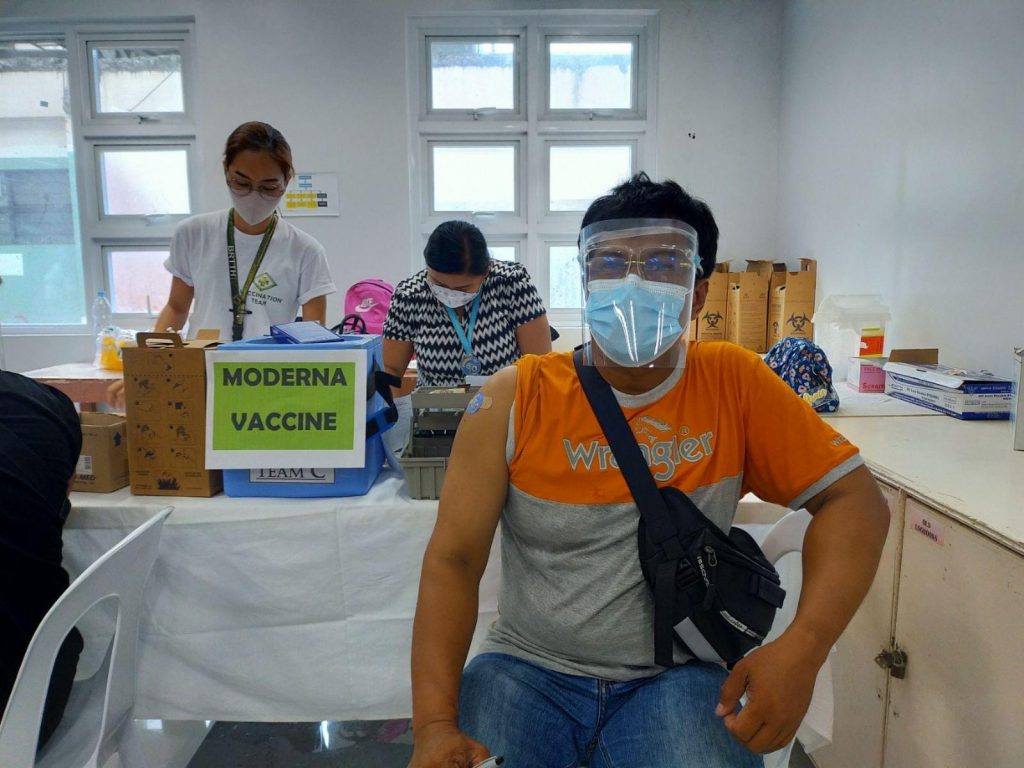 Filipino wearing face shield and mask, in waiting room after getting moderna vaccine